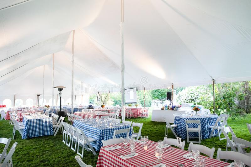 Wedding or special event tables set up for an outdoor barbeque with red and blue checkered table clothes under an event tent royalty free stock images