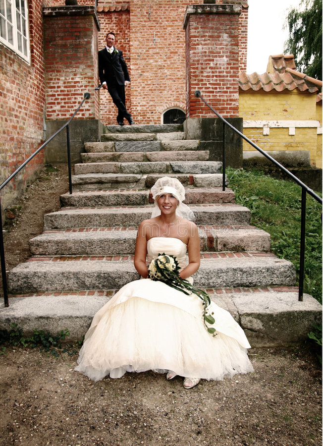 Wedding stairs. Wedding couple portrait. groom and bride marriage celebration. husband in suit and wife in wedding dress sat on stairs stock photo