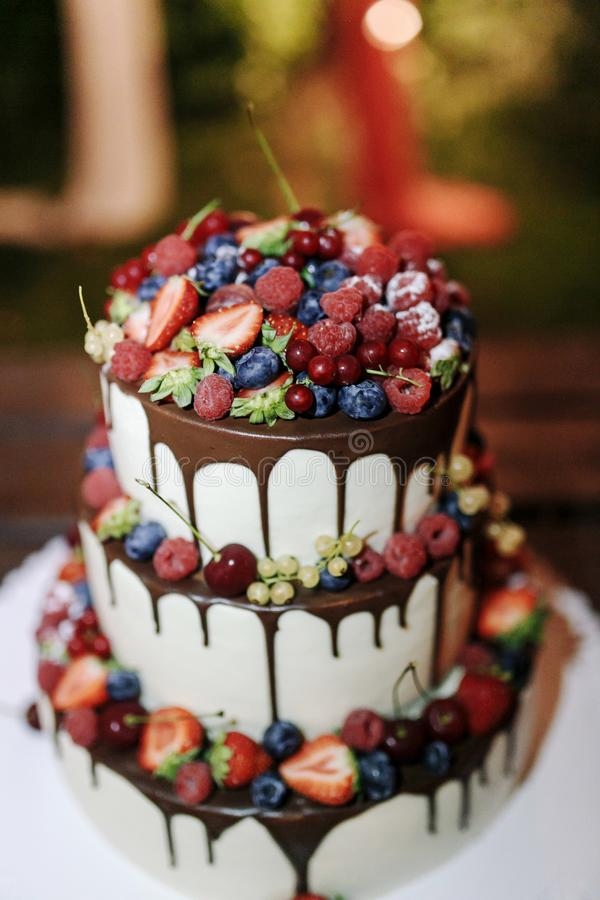 Wedding Strawberry blueberry raspberry berries cake with chocolate on a wooden background in evening outdoor. Close up royalty free stock images