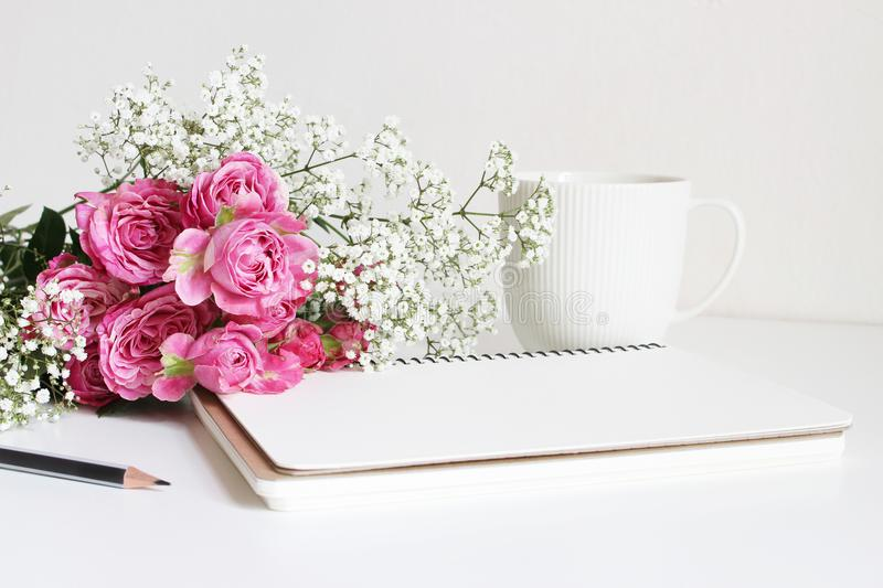 Wedding styled stock photo. Still life with pink roses, baby`s breath Gypsophila flowers, white cup, pencil and notebook. Floral composition. Image for blog or stock image