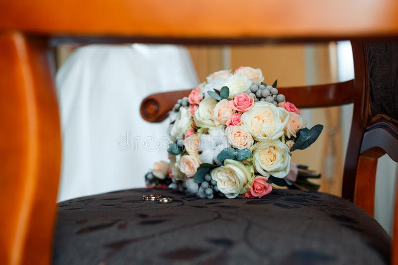 Wedding stylish bouquet with purple roses and rings. royalty free stock image