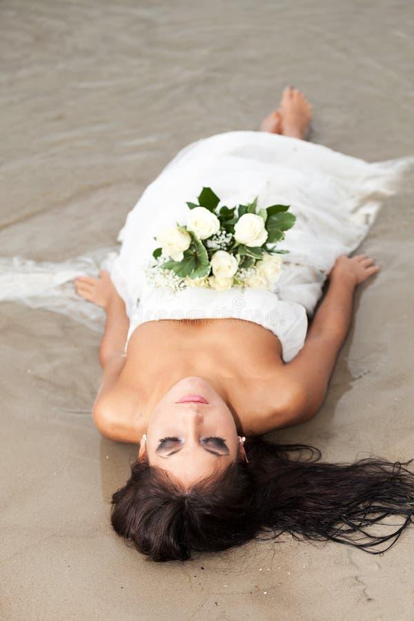 Wedding survivor. Tired bride on a beach stock photos