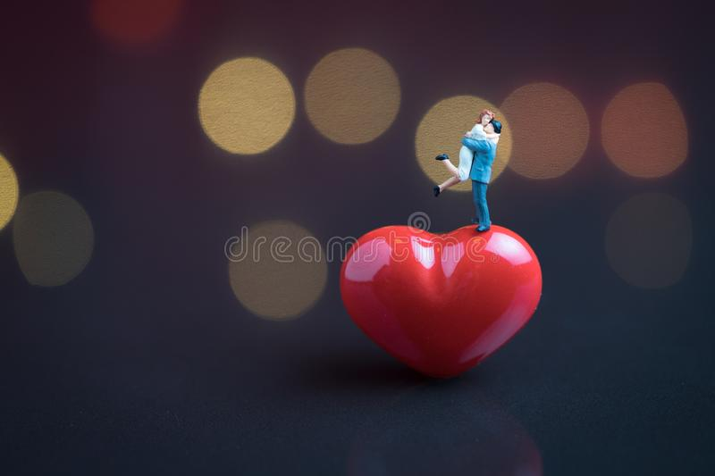 Wedding sweet romantic night concept, happy miniature couple holding and standing on red heart shape with soft low key dark stock photos
