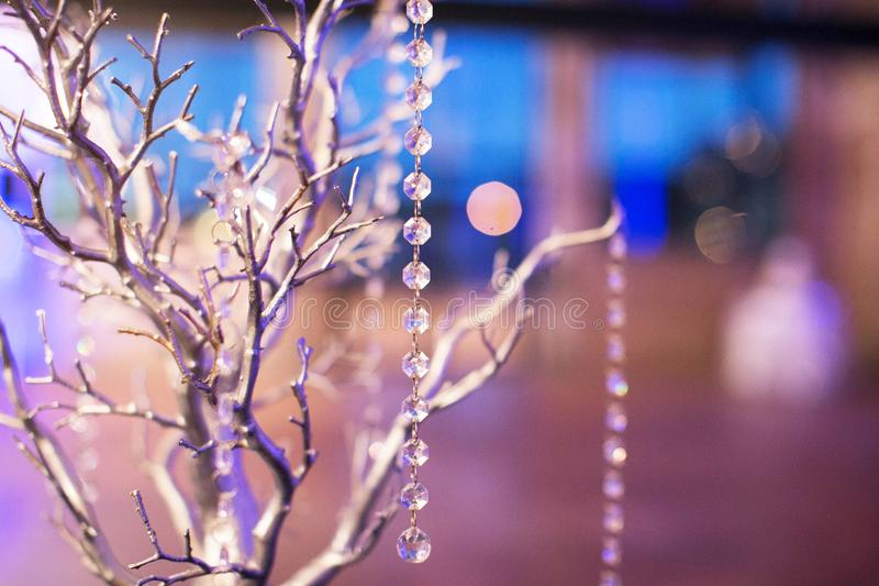 Wedding Table Arrangement - Silver Tree with Glass String Beads. With beautiful blue light and bokeh in the background stock image