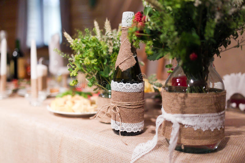 Wedding table. Bottles of champagne wine dressed in wedding gowns royalty free stock photography