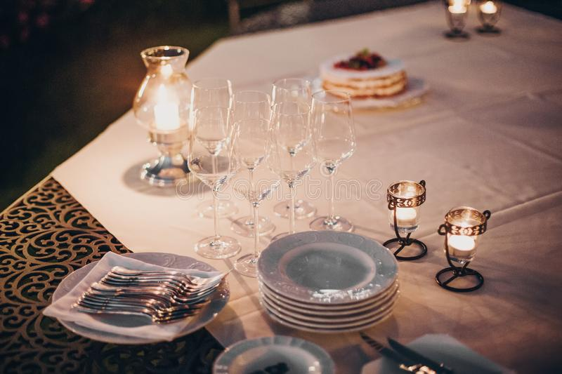 Wedding table with candles, cutlery and plates, champagne drink and glasses at reception outdoors in the evening. Luxury catering. At  celebration in soft royalty free stock photos