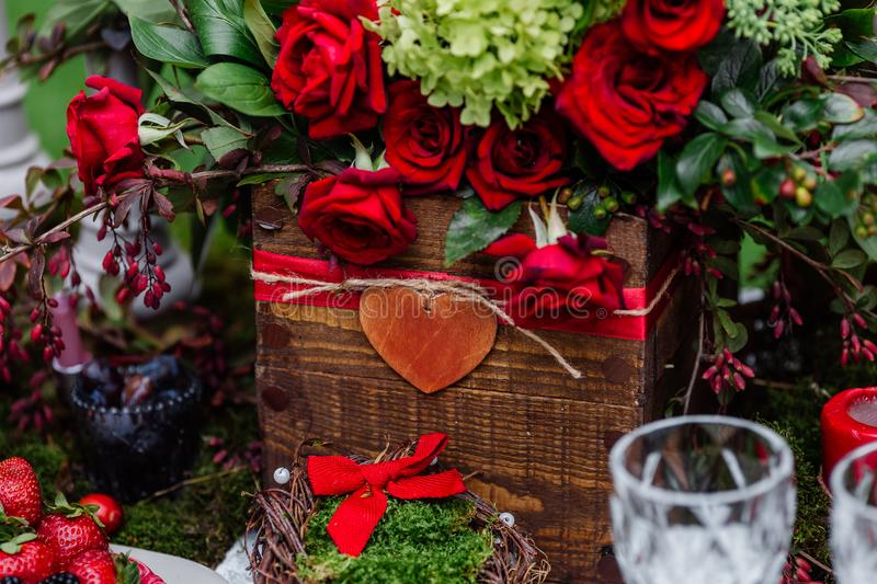 Wedding table decor: flowers composition with roses,berries, herbs and greenery standing in wooden box. Bridal details and decorat royalty free stock photo