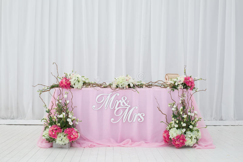 Wedding table. Decorated with flowers. Mr & Mrs lettering. large place for your text or logo over the table stock photo