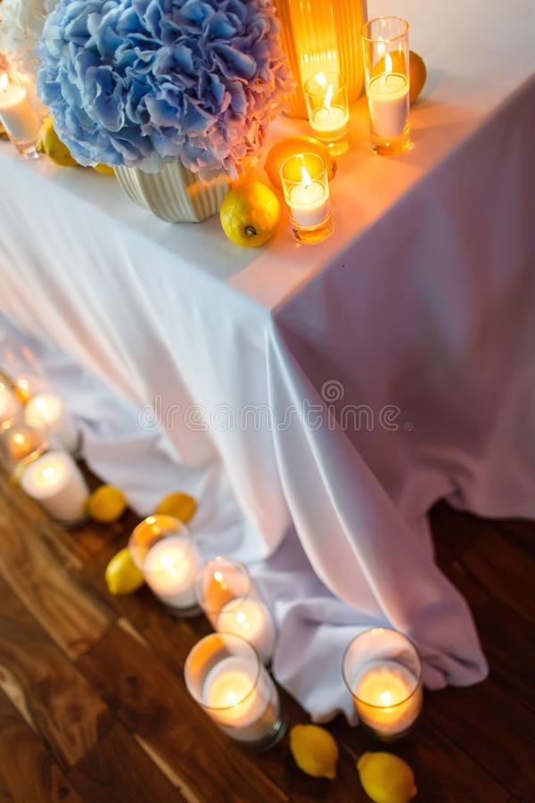 Wedding table decoration with candles and blue flowers stock images