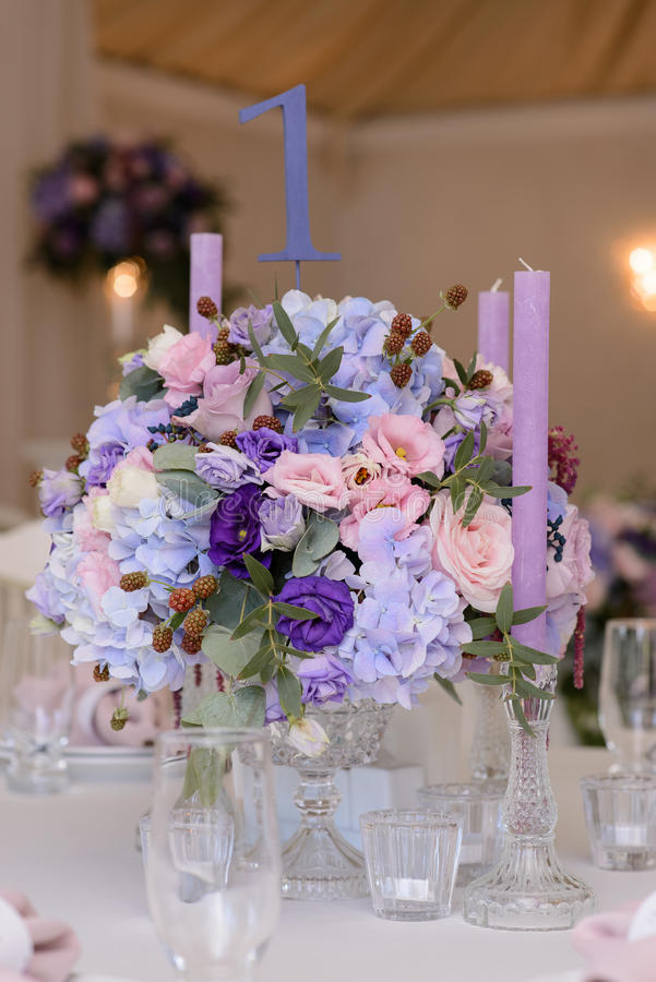Wedding table decoration with violet, blue, pink flowers and greenery royalty free stock photos