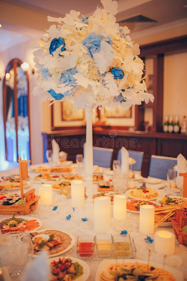Wedding table decorations. Candles and white and blue flowers stock image