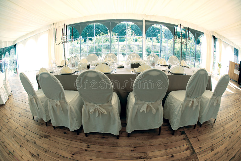 Wedding table fisheye effect. Wedding table photographed with a fisheye lens effect. Very curved view with the chairs, table, and wooden panel flooring visible stock photography