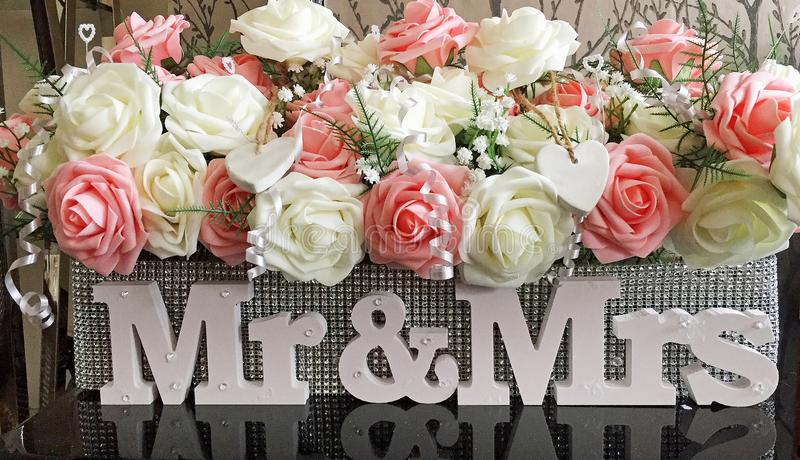 Wedding table floral oasis covered in glitter with mr & mrs. Mr and Mrs letters against a sequinned oasis covered with pretty peach and white flowers and hearts stock photography