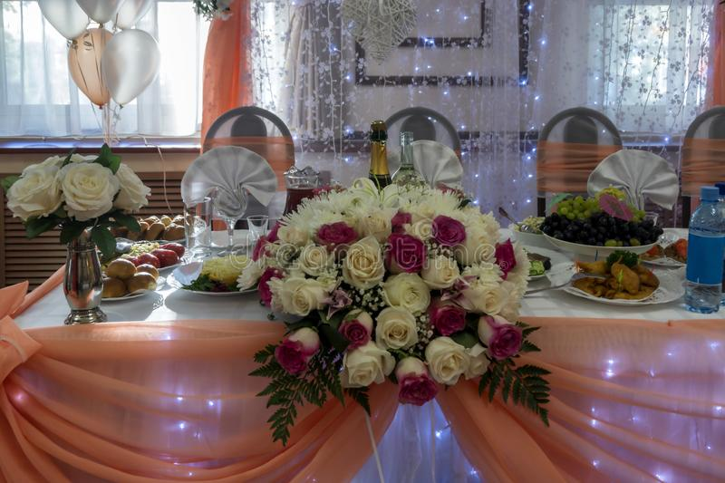 Wedding table decorated with balloons, lights and other decorations. Wedding table with flowers and lights decorations, champagne and food on festive table royalty free stock images