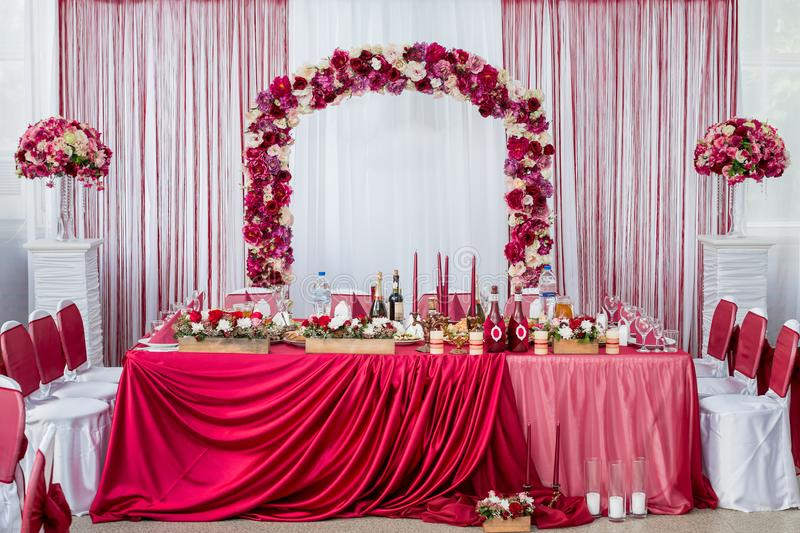 Wedding table for the newlyweds. decorated with fresh flowers and a red tablecloth royalty free stock photography