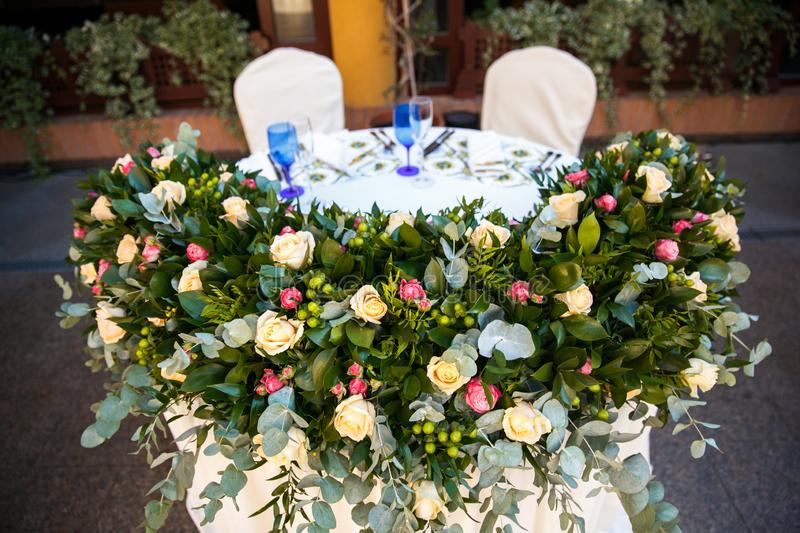 The wedding table of the newlyweds is decorated with roses royalty free stock photo