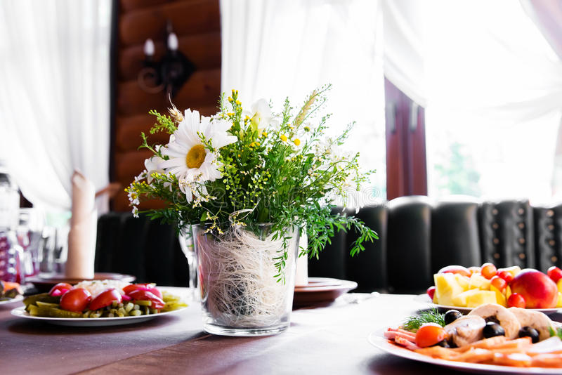 Wedding table in restaurant with flower composition stock photos