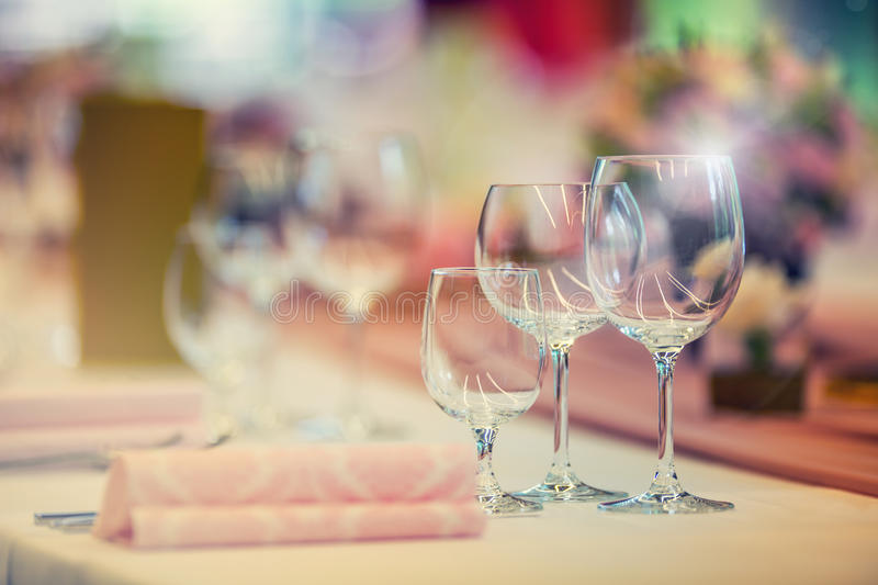 Wedding table setting. Beautiful table set with flowers and glass cups for some festive event, party or wedding reception stock photos