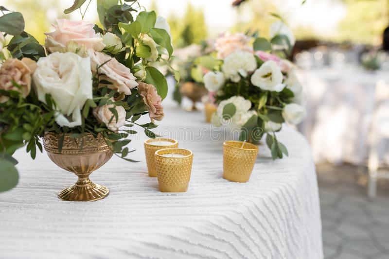 Wedding table setting decorated with fresh flowers in a brass vase. Wedding floristry. Banquet table for guests outdoors with a. View of green nature. Bouquet stock photography