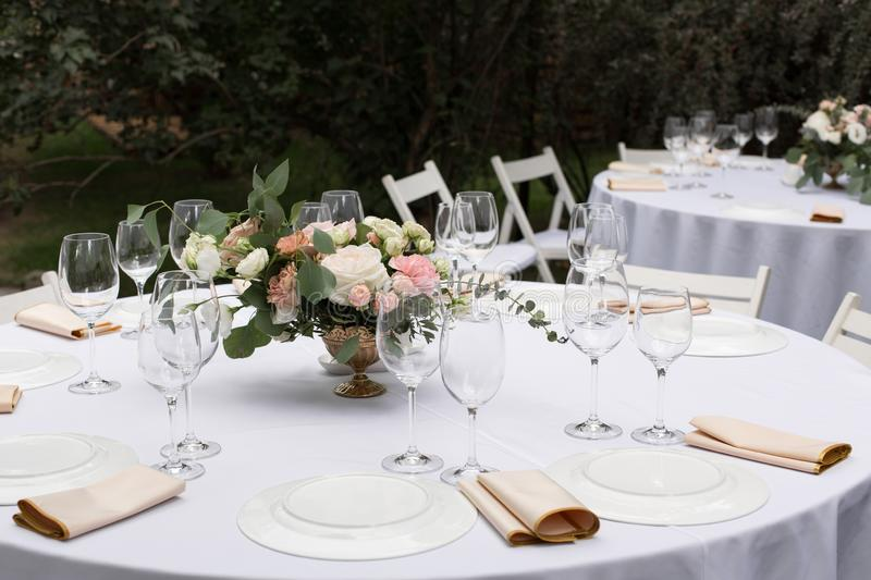 Wedding table setting decorated with fresh flowers in a brass vase. Wedding floristry. Banquet table for guests outdoors with a. View of green nature. Bouquet stock image