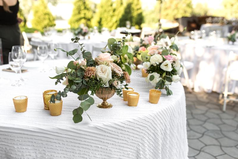 Wedding table setting decorated with fresh flowers in a brass vase. Wedding floristry. Banquet table for guests outdoors with a. View of green nature. Bouquet royalty free stock images