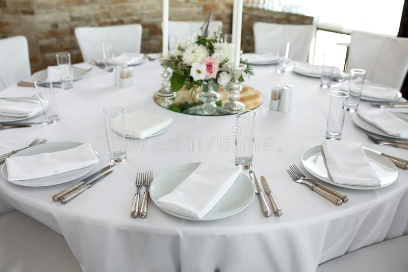 Wedding table setting decorated with fresh flowers. White plates, silverware, white tablecloth and white room. Wedding floristry. Banquet table for guests royalty free stock photo