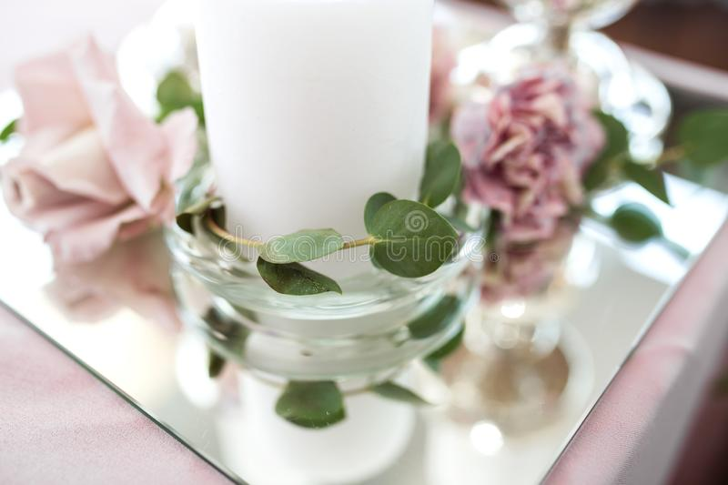 Wedding table setting newlyweds decorated with fresh flowers. White plates, silverware, white candles and a pink tablecloth. Wedding floristry royalty free stock images