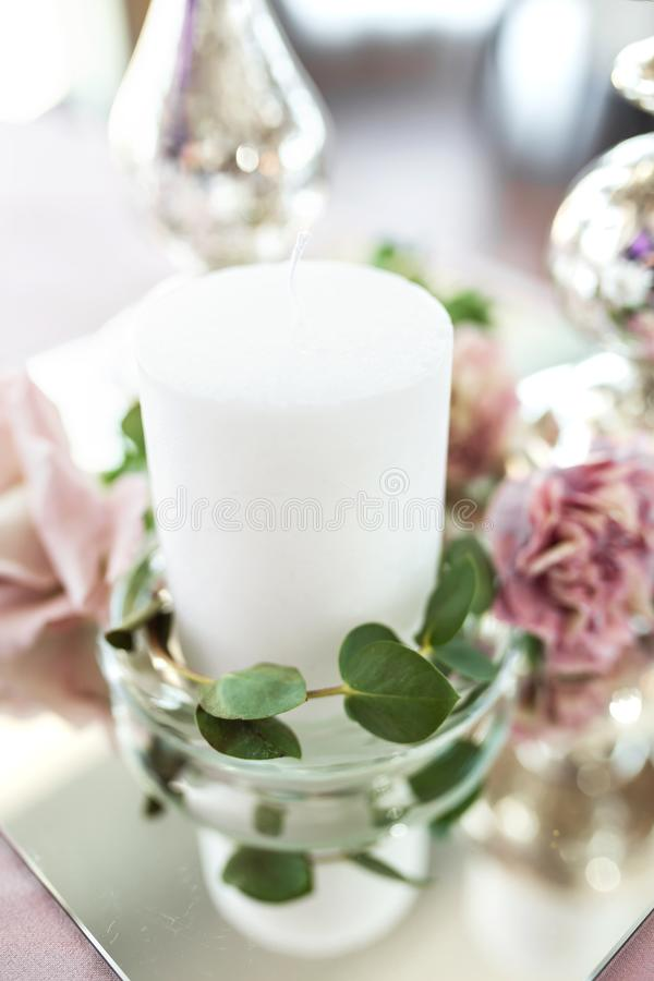 Wedding table setting newlyweds decorated with fresh flowers. White plates, silverware, white candles and a pink tablecloth. Wedding floristry royalty free stock photos