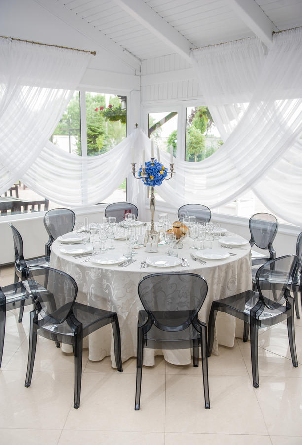 Wedding table setting. Table set for an event party or wedding reception. Elegant table setting in restaurant with a blue bouquet stock photography