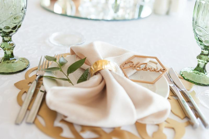 Wedding table setting, tableware for the newlyweds, on a plate a napkin and a rustic sign word - bride or groom stock image