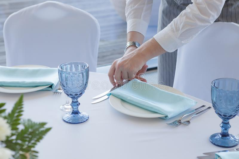 Wedding table setting. The waiter in a gray suit and white shirt serves the table stock image