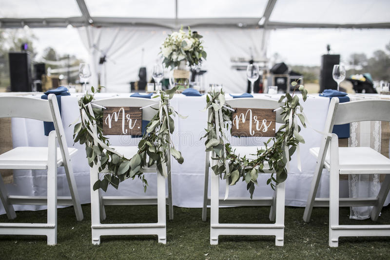 Wedding table under tent, with Mr and Mrs signs. On the chairs royalty free stock photo