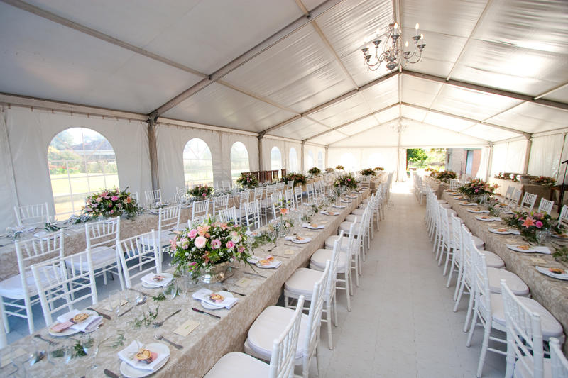 Wedding tent. The inside of a massive white wedding tent with tables and chairs already in position royalty free stock images