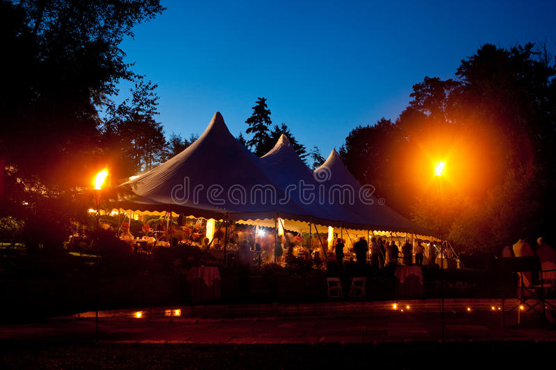 Wedding tent at night. Beautiful wedding tent set up for an outdoor reception. This is a long night exposure, there is blur under the tent showing activity stock images