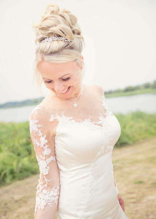 Bride smiling. Wedding theme, bride outdoors moving around ,smiling and looking sideways royalty free stock photos