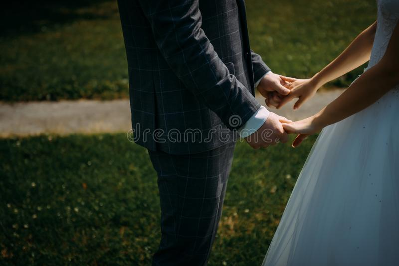Wedding theme, holding hands newlyweds on green grass background. Hands of the bride and groom close-up. A couple on their wedding stock image