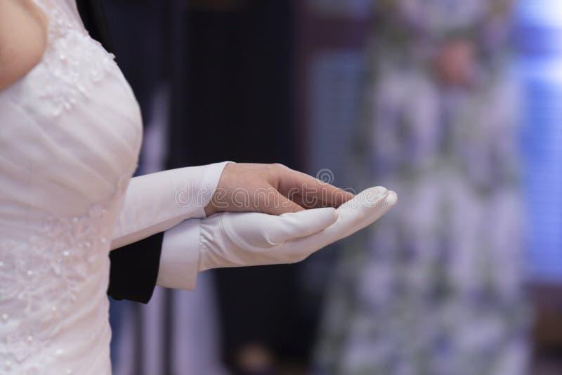 Wedding theme, holding hands newlyweds White gloves stock image