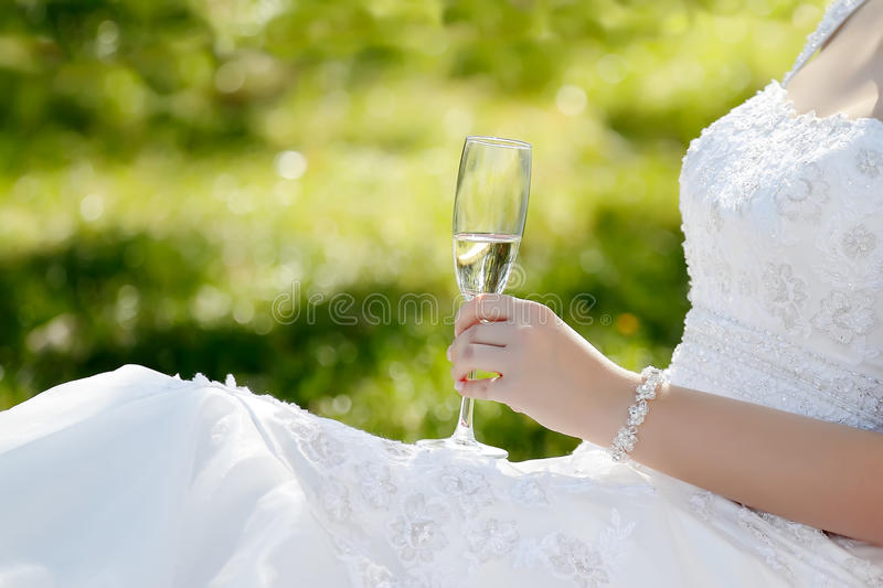Wedding toast. Woman wedding hand with glass on landscape orientation photo, focused to glass royalty free stock photo