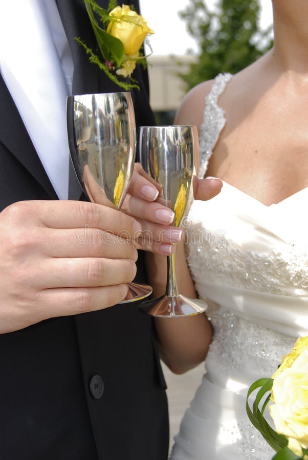 Wedding toast. Womans and mans wedding hands with glasses stock photos