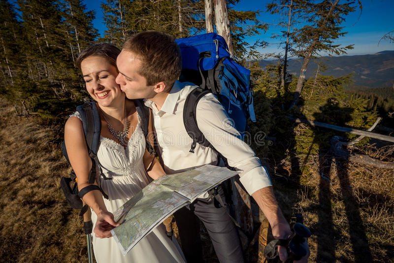 Wedding tourist couple kissing with map in hands. Honeymoon at the mountains. Wedding tourist couple with map kissing. Honeymoon in the mountains stock photo