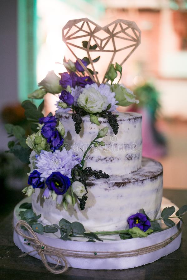 Wedding two-tiered white cake with flowers and a decorative heart royalty free stock photography