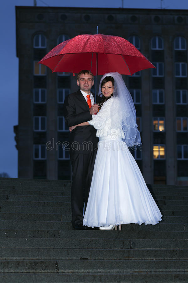 Wedding under the rain. Just married couple with umbrella under the rain stock image