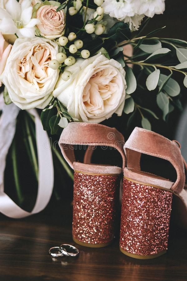 Wedding velvet pink shoes with shiny beautiful heels with gold wedding rings beside a bouquet of white roses, eucalyptus on a dark. Wooden background. Vertical royalty free stock images