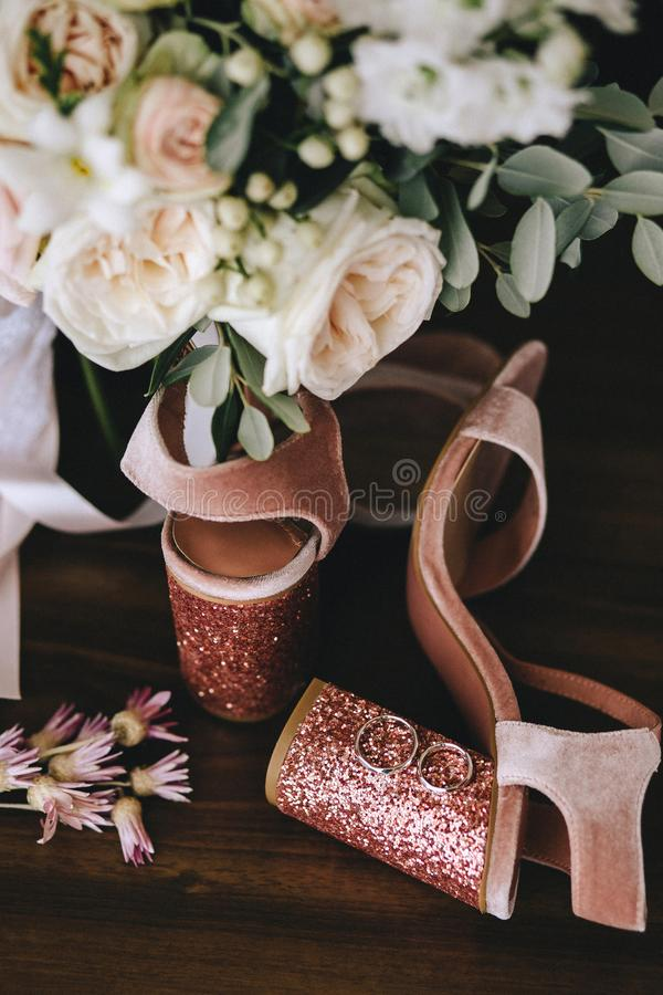 Wedding velvet pink shoes with shiny beautiful heels with gold wedding rings beside a bouquet of white roses, eucalyptus on a dark stock photography