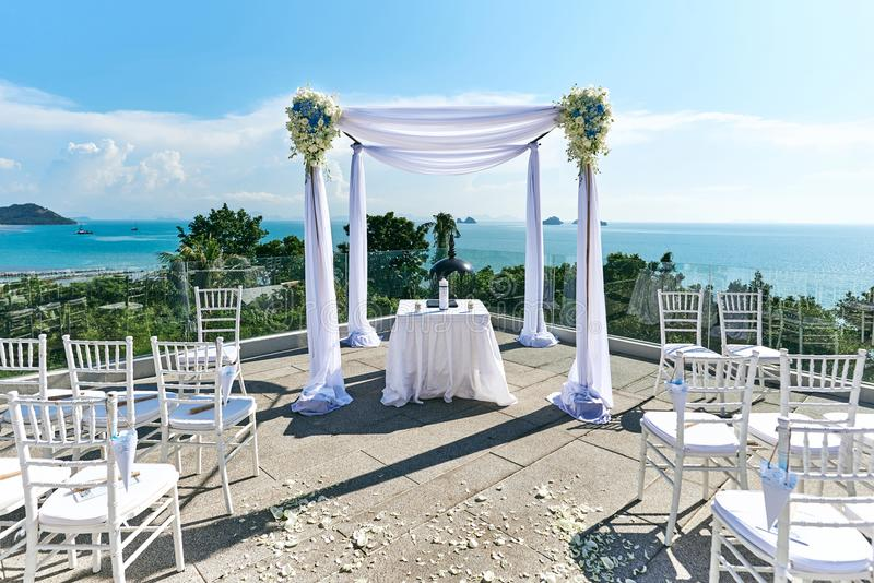 Wedding venue setting, Arch and altar decorated with roses, flowers, ocean background. The wedding venue setup on the hill with panoramic ocean view, White stock photo