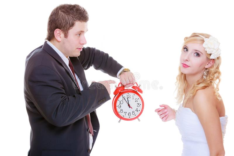 Groom holding big red clock yelling and bride. Wedding, waiting for celebration and proposal, negative bad relationship concept. Groom holding bid red clock stock photo