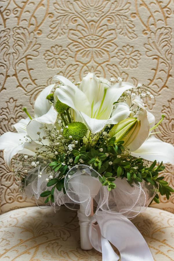 Wedding white bride shoes with a bouquet of white roses and other flowers, wedding rings on a stool stock images