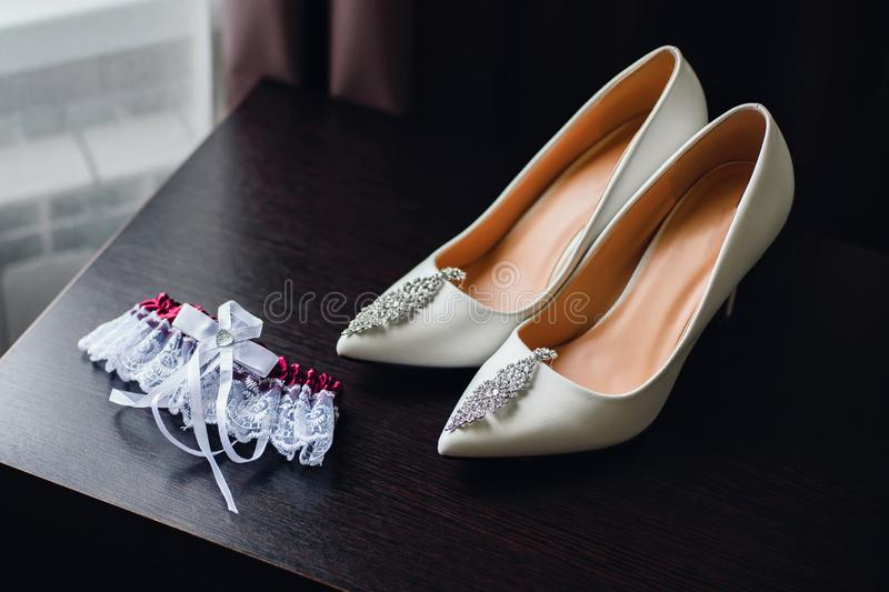 Wedding white bride shoes with silver earrings. On the table stock image