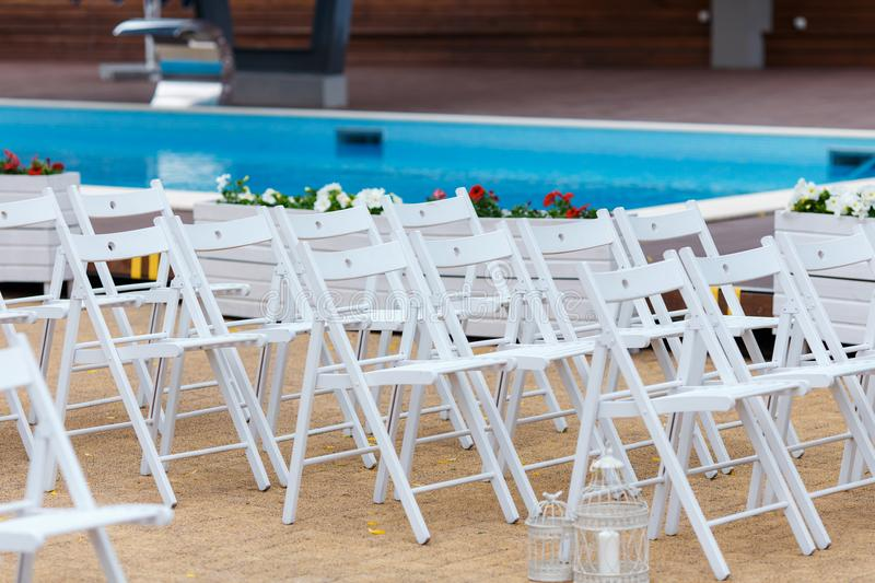Wedding white chairs. Seating in front of the wedding ceremony venue royalty free stock photo