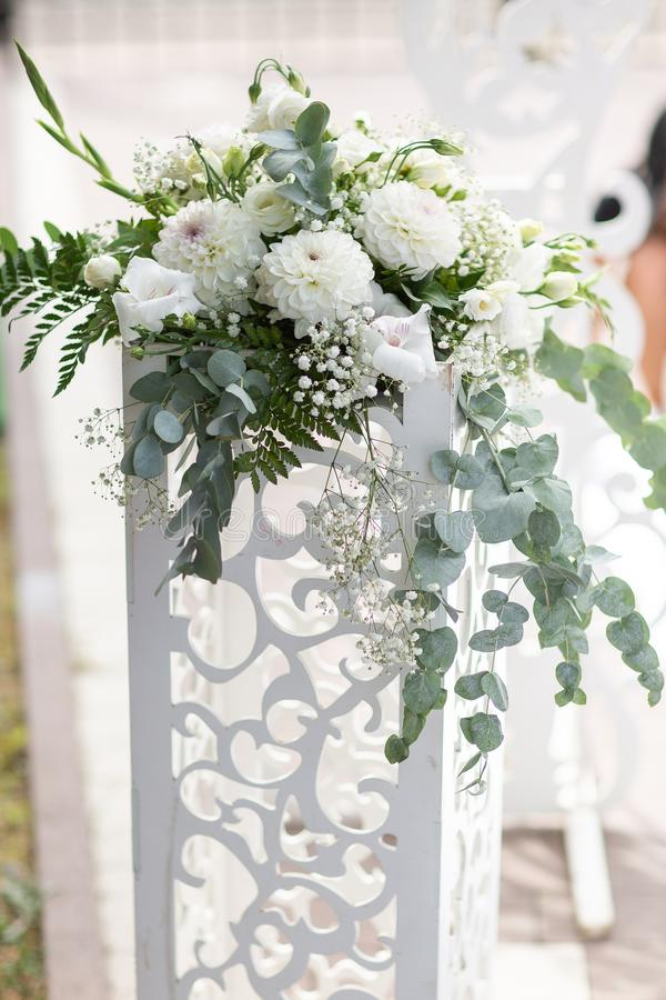 Wedding white wooden arch decorated with flowers outdoors. Beautiful wedding set up. Wedding ceremony on green lawn in the garden. Part of the festive decor royalty free stock photos